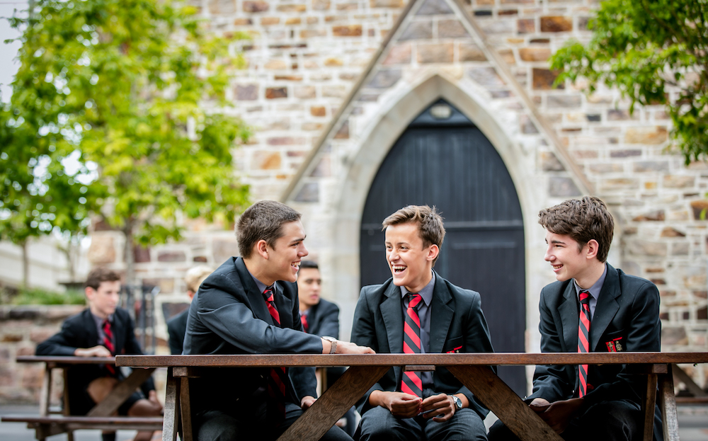 Three school students sitting and talking in front of old chapel