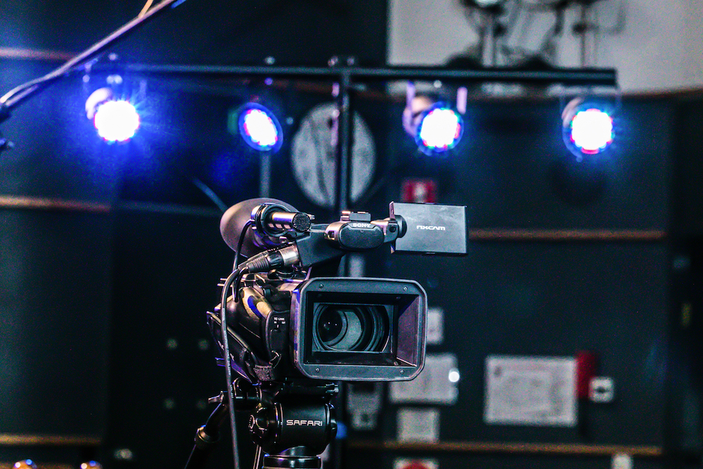 A video camera with stage lights in the background